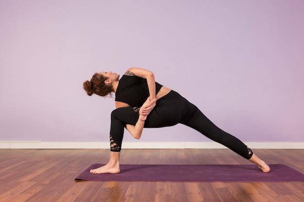 Hermosa joven practicando yoga en el interior