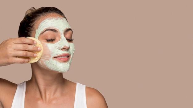 Hermosa joven probando productos cosméticos