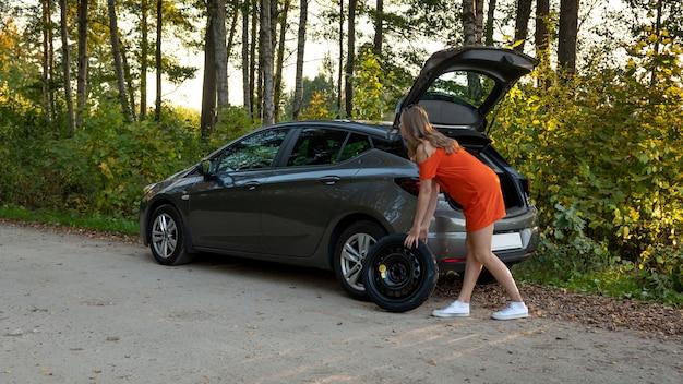 Una hermosa joven quita la rueda de repuesto del maletero del automóvil