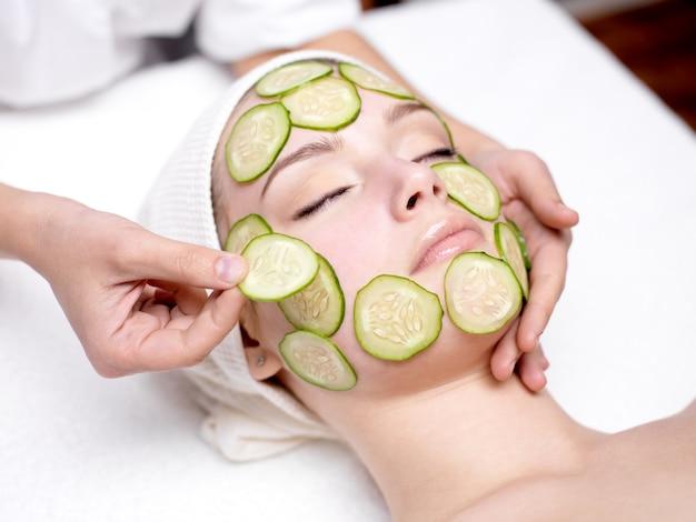 Hermosa joven receibing mascarilla facial de pepino en salón de belleza