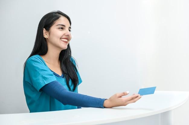 Hermosa joven recepcionista con una gran sonrisa dando una tarjeta de visita.