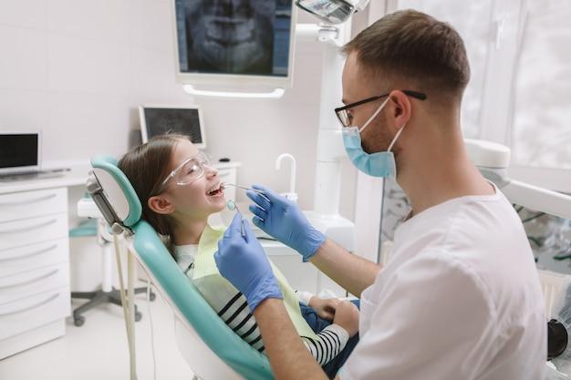 Hermosa joven recibiendo chequeo dental por dentista experimentado
