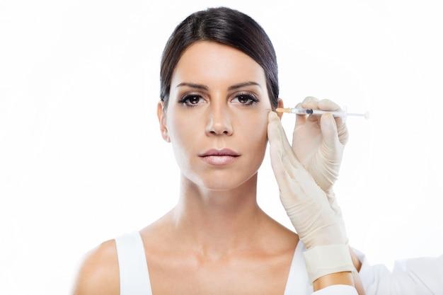 Hermosa joven recibiendo inyección cosmética de botox en su rostro.