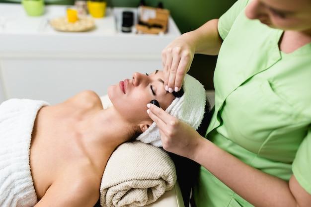Hermosa joven recibiendo masaje facial con piedras calientes en el spa de belleza. terapia lastone.
