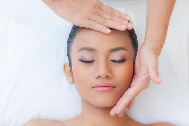 Hermosa joven recibiendo masajes en el salón de spa