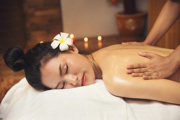 Hermosa joven recibiendo salón de masaje spa y flor blanca en su oreja.