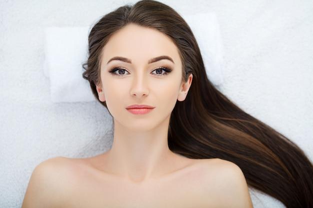 Hermosa joven recibiendo un tratamiento facial en el salón de belleza