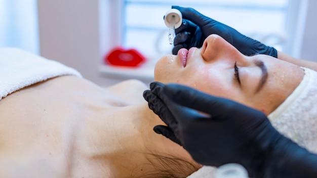 Hermosa joven recibiendo un tratamiento facial en el salón de belleza.