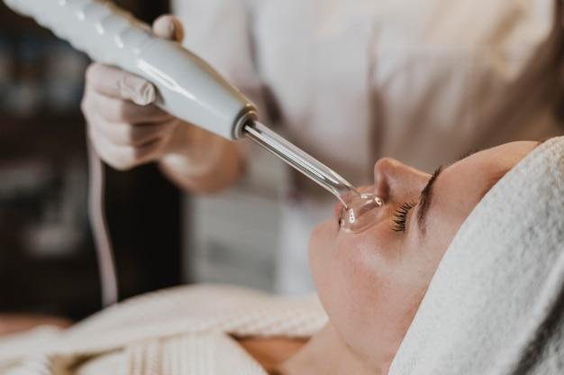 Hermosa joven recibiendo un tratamiento facial en el spa