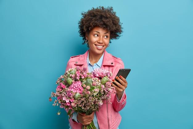 Hermosa joven reflexiva recibe felicitaciones en el teléfono inteligente celebra cumpleaños obtiene un bonito ramo de flores