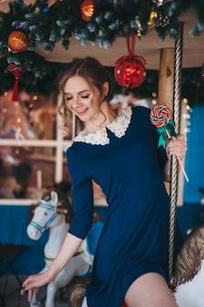 Hermosa joven se regocija cerca de un carrusel con caballos. navidad.