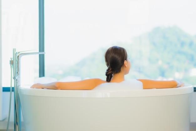 Hermosa joven relajante en la bañera.