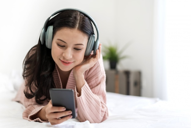 Hermosa joven relajante escuchando música con auriculares en la cama en su casa