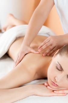 Hermosa joven relajante con masaje de manos en el spa durante un tratamiento de belleza