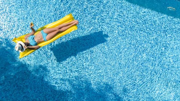 Hermosa joven relajante en la piscina, la mujer nada en un colchón inflable y se divierte en el agua en vacaciones familiares