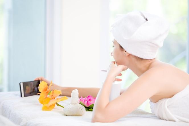 Hermosa joven relajante salón de spa con selfi en teléfono móvil en el balneario