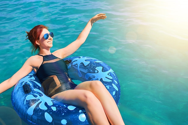 Hermosa joven relajarse en anillo inflable en agua de mar