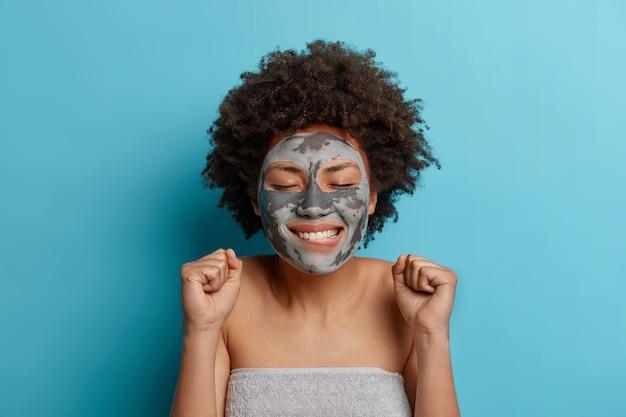 Hermosa joven rizada se preocupa por la tez aplica mascarilla de arcilla para el rejuvenecimiento de la piel cierra los ojos y sonríe