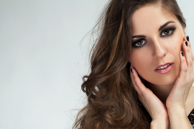 Hermosa joven con rizos y maquillaje