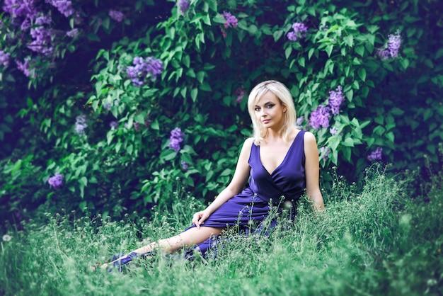 Hermosa joven rodeada de flores de color púrpura. la mujer está sentada con un vestido largo con una hendidura en el fondo de un jardín de primavera con lilas