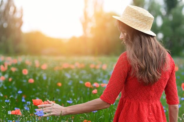 Hermosa joven romántica en sombrero de paja caminando sobre un campo de flores de amapola y toma amapolas