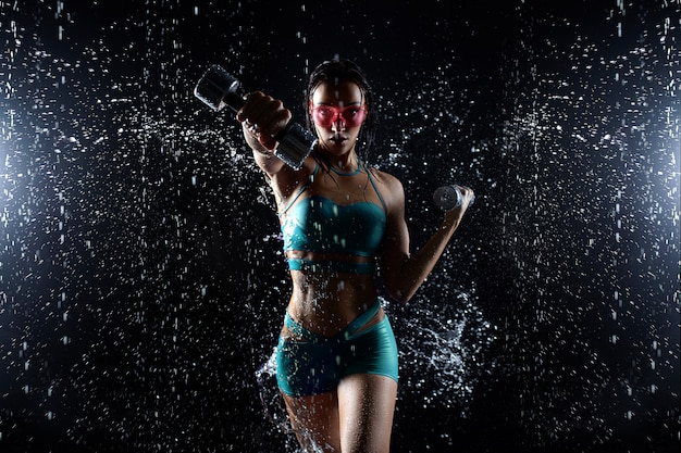 Hermosa joven en ropa deportiva posa con pesas en aqua studio