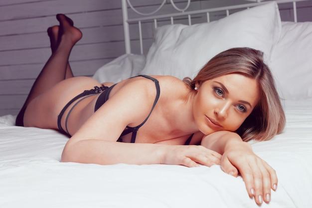 Hermosa joven en ropa interior negro posando en la cama de cerca