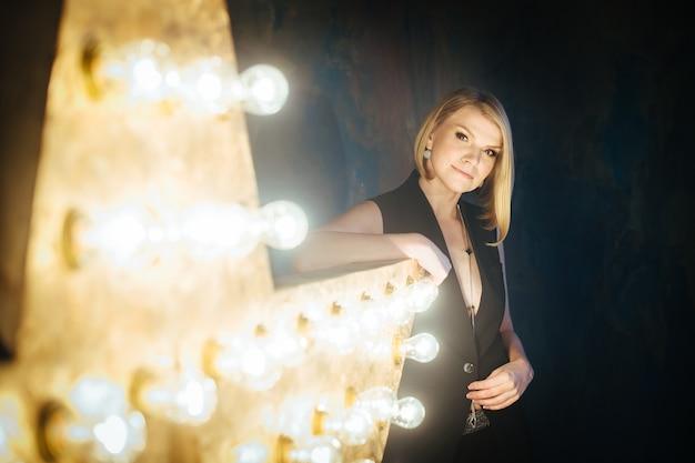 Hermosa joven rubia en el fondo de las lámparas de una estrella.
