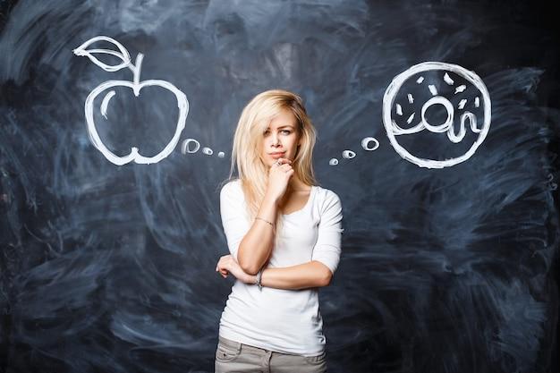 Hermosa joven rubia hace una elección entre una manzana y un donut en el fondo de una pizarra. concepto de alimentación saludable