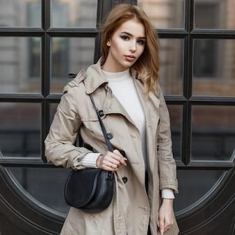 Hermosa joven rubia de moda con un abrigo de primavera con un bolso de cuero negro de moda en una bata blanca de pie cerca de la puerta del espejo del hotel. chica europea con estilo.