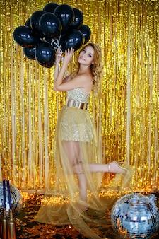 Hermosa joven rubia modelo en un elegante vestido dorado con un fondo de cuernos de aro de cintas de loto con guirnaldas se encuentra en el piso sostiene en sus manos un montón de bolas negras.