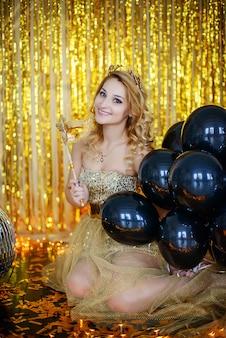 Hermosa joven rubia modelo sonriente tiene en sus manos una máscara de carnaval en un elegante vestido dorado con un fondo de cuernos de aro de cintas de loto.