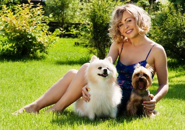 Una hermosa joven rubia en el parque con perros