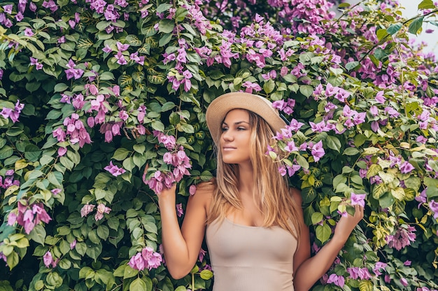 Hermosa joven rubia posando con flores tropicales