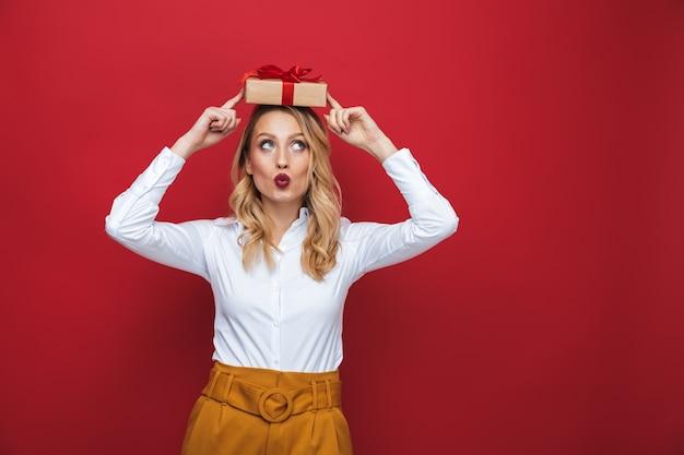 Hermosa joven rubia que se encuentran aisladas sobre fondo rojo, sosteniendo una caja de regalo en la cabeza