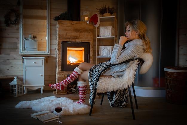 Hermosa joven rubia relajante en acogedora cabaña de montaña