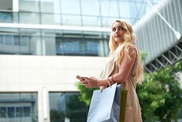 Hermosa joven rubia con smartphone en la calle