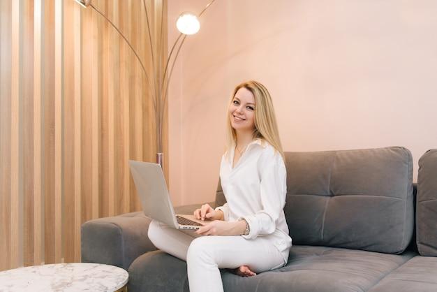 Hermosa joven rubia sonriente con portátil en casa en el sofá, trabajo remoto desde casa, aislamiento