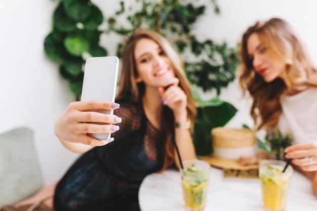 Hermosa joven rubia en traje elegante tomando una foto de sí misma mientras pasa tiempo con un amigo en el café