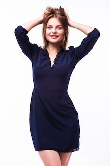 Hermosa joven rubia en vestido negro de pie sobre fondo gris