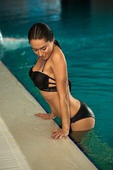 Hermosa joven saliendo de la piscina en el spa center