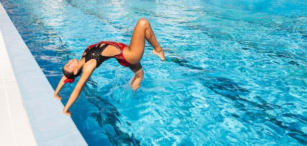 Hermosa joven saltando en el agua