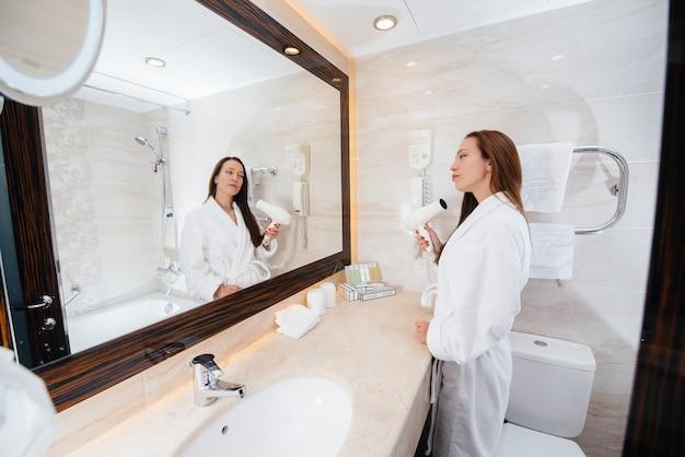 Una hermosa joven se seca el cabello con un secador de pelo en un hermoso baño blanco. buenos días frescos en el hotel.