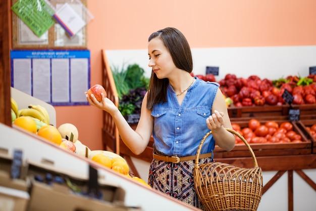 Hermosa joven selecciona manzanas en una tienda de verduras