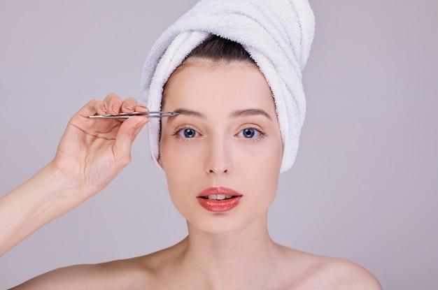 Hermosa joven semidesnuda depilarse las cejas con pinzas.