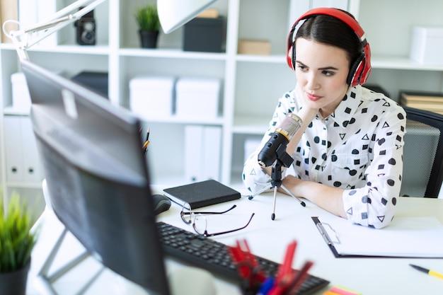 Hermosa joven sentada en auriculares y con micrófono en la mesa en la oficina y hablando.