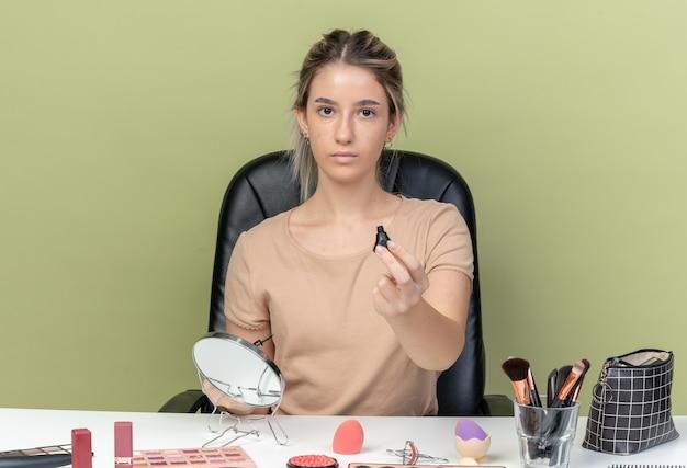 Hermosa joven sentada en un escritorio con herramientas de maquillaje sosteniendo rímel en la cámara aislada en la pared verde oliva