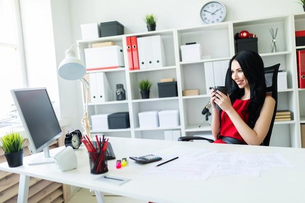 Hermosa joven sentada en la oficina en la mesa y sosteniendo un vaso de café.