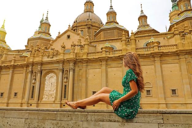 Hermosa joven sentada en la pared con la basílica en zaragoza, españa