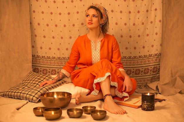 Hermosa joven sentada en posición de yoga y meditación con cuencos y velas